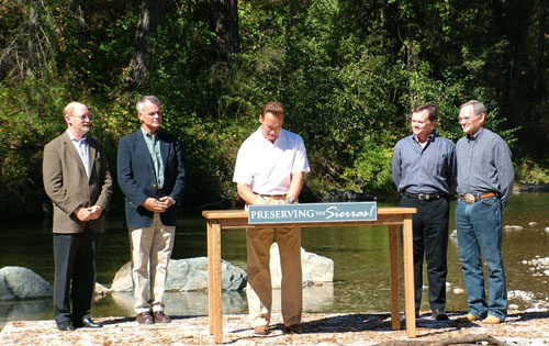 """Gov. Schwarzenegger signs the Sierra Nevada Conservancy at the Bear River in Colfax, calling the Sierras """"the crown jewel"""" of California. Assemblyman Laird, Resources Secretary Chrisman, CalEPA Secretary Tamminen, and Assemblyman Leslie look on."""