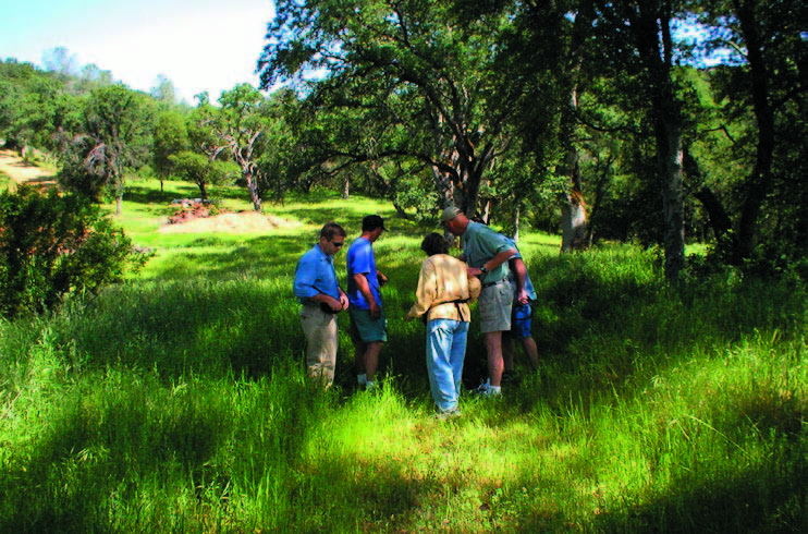 """This issue's """"From the Board Room"""" refl ects the old adage that a picture is worth a thousand words. Land stewardship is a challenging yet rewarding obligation of PLT's work ... it's nice to get out in the fi eld here in Placer County! Pictured above are PLT Board members and volunteers on a monitoring visit to one of our easement proper- ties, gathered around one of the reptilian residents of the protected property."""